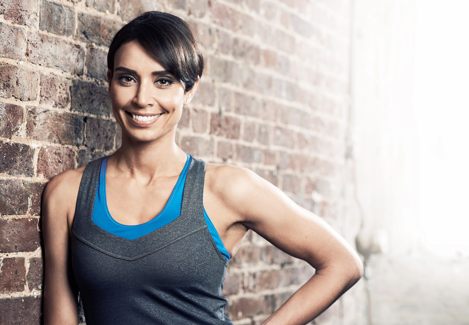 Christine Bleakley photographed leaning against a brick wall in a gym
