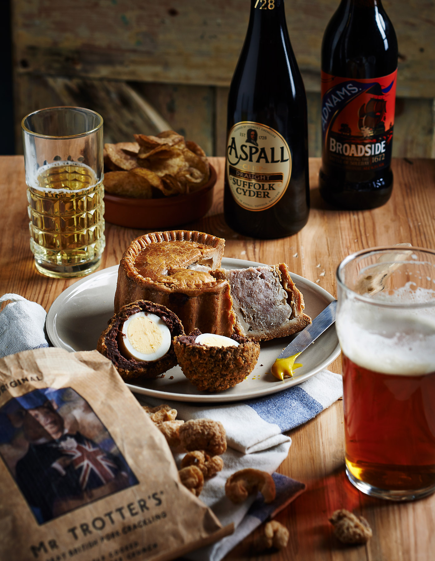 Pub table with beer, cider, pork pie and crisps