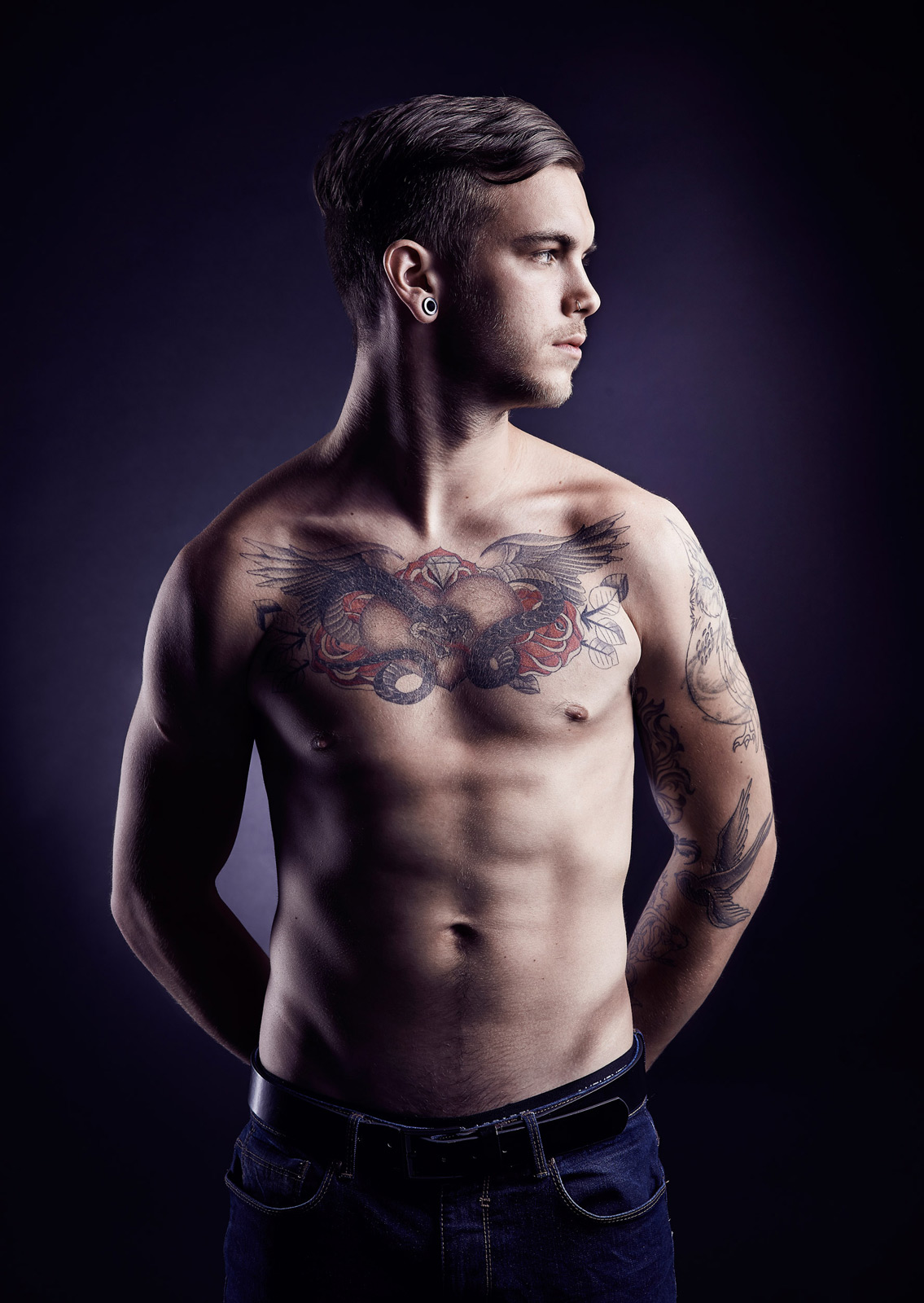 Man with shirt off showing tattoos