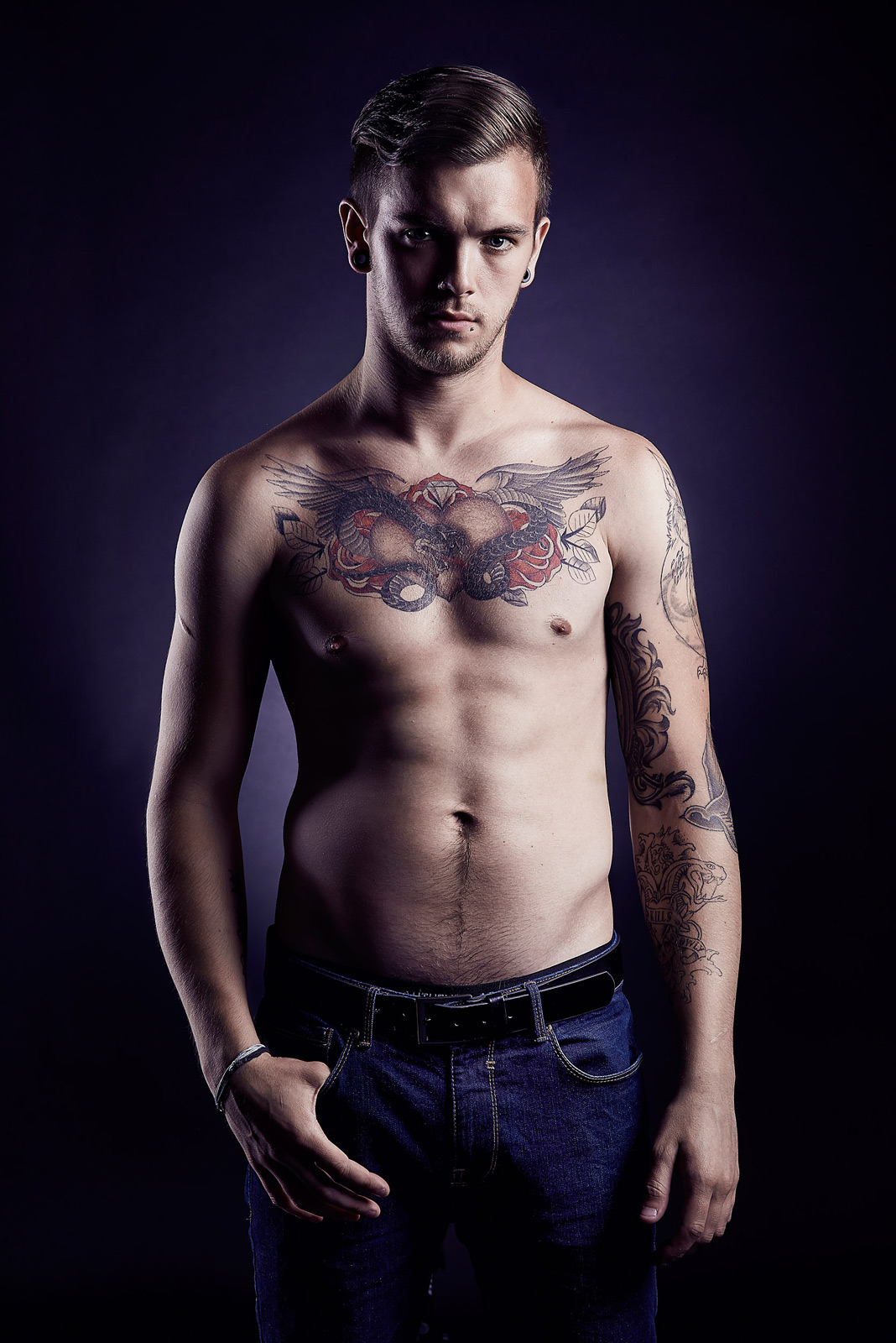 Man with shirt off showing tattoos and looking at the camera