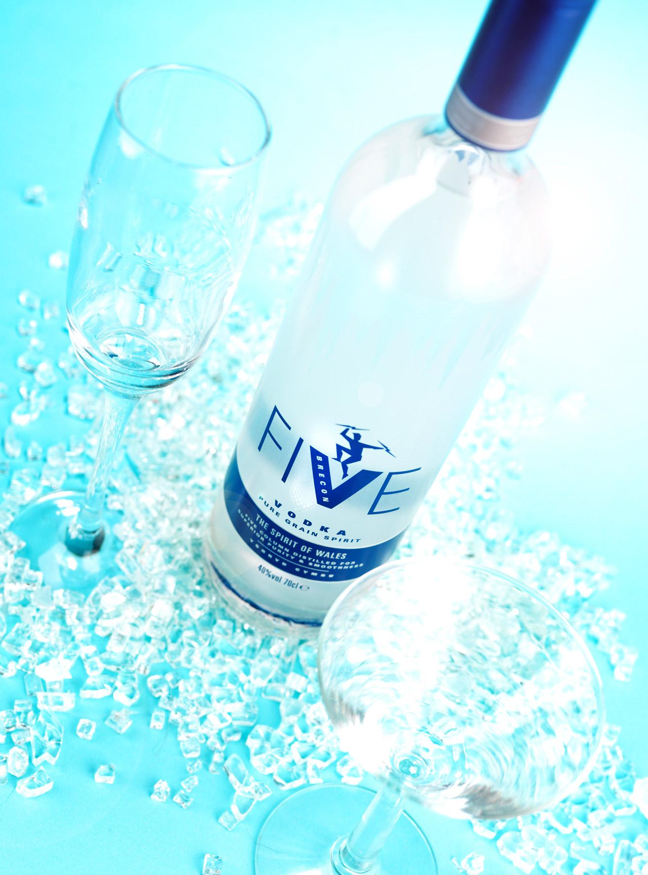 Vodka bottle shot from above on a blue background