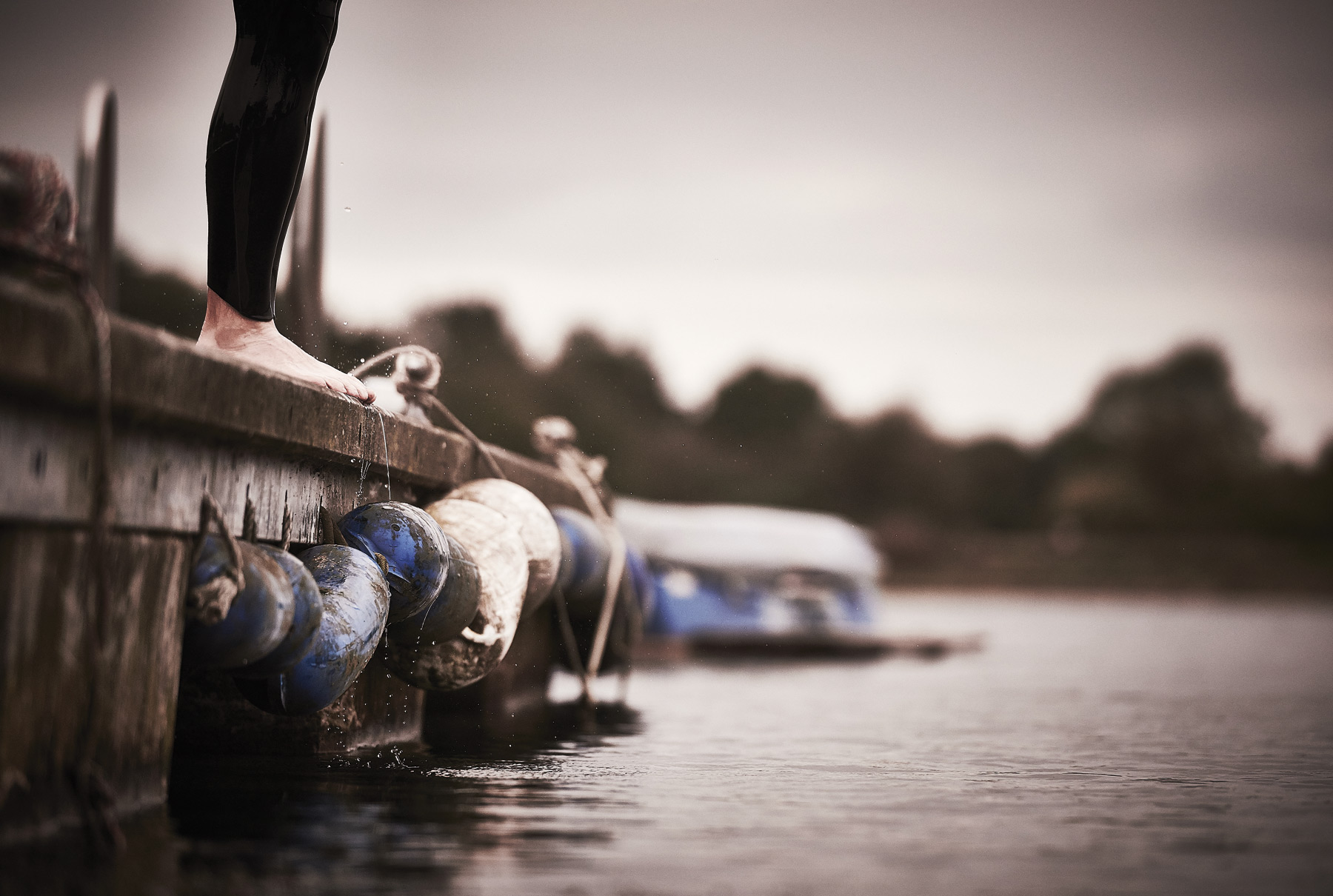 A man's feet as he prepares to jump into open water