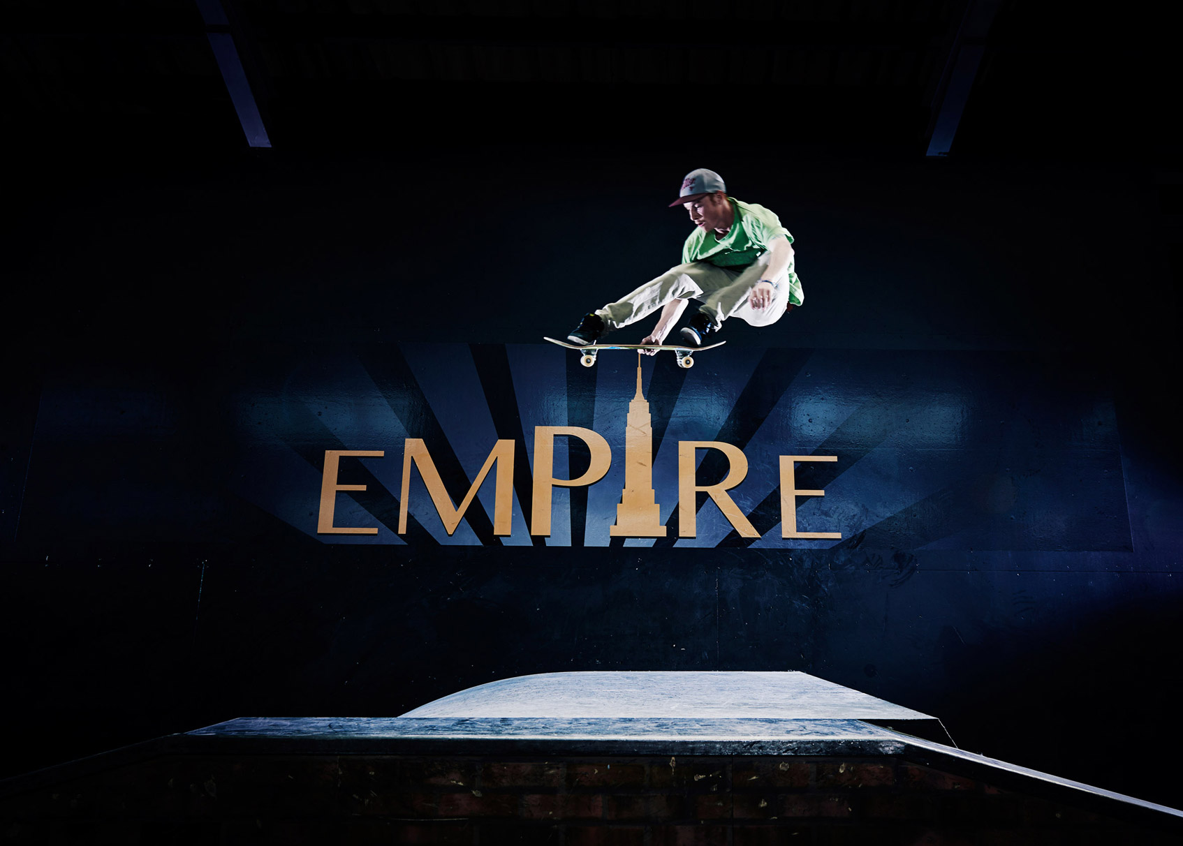Skateboarder jumps over the Empire logo