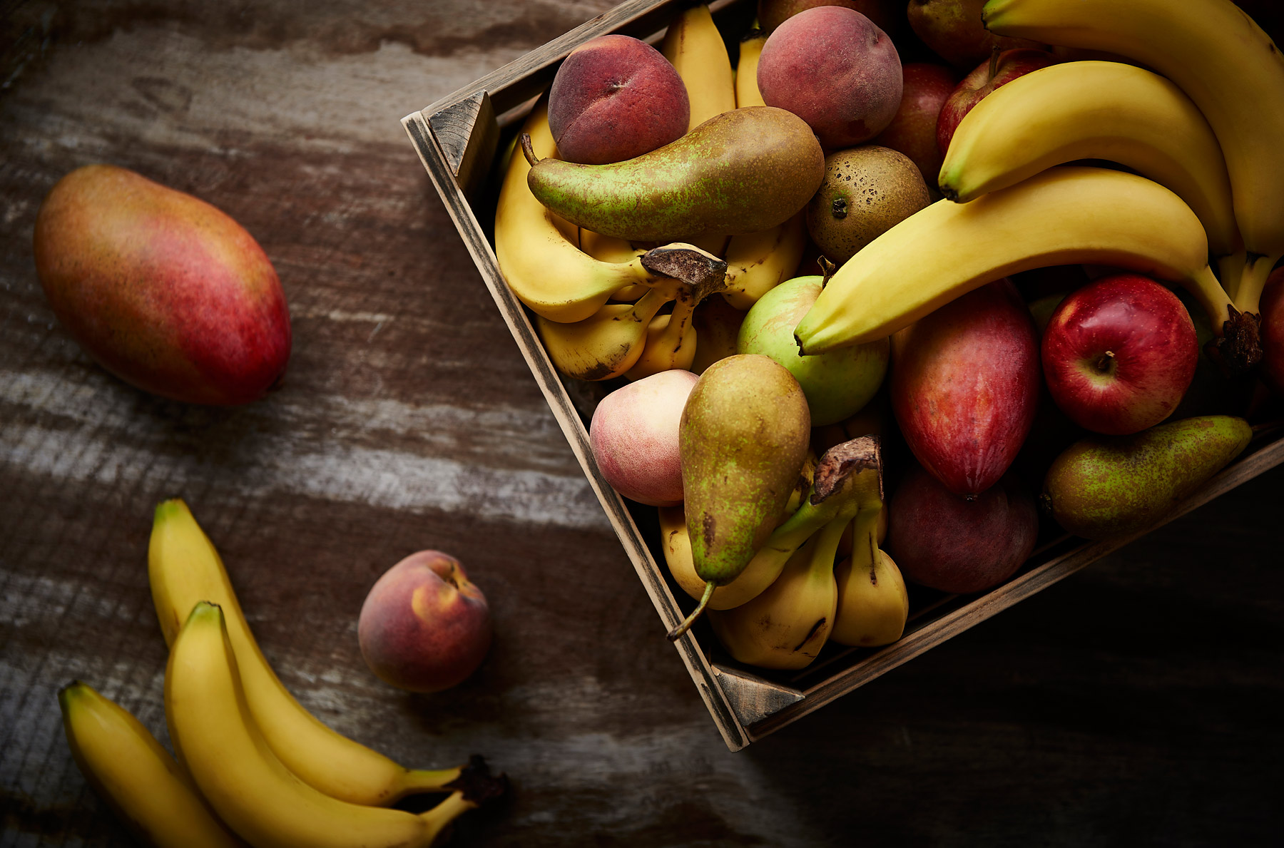 A crate of bananas, apples, pears and other fruit on a wooden background