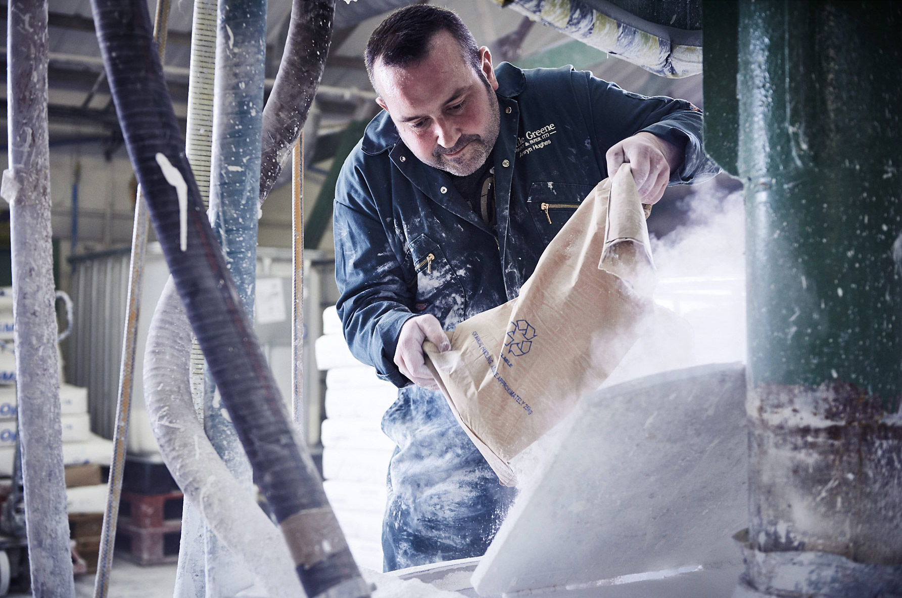 Paint factory photoshoot – a worker pours in the basic starting materials