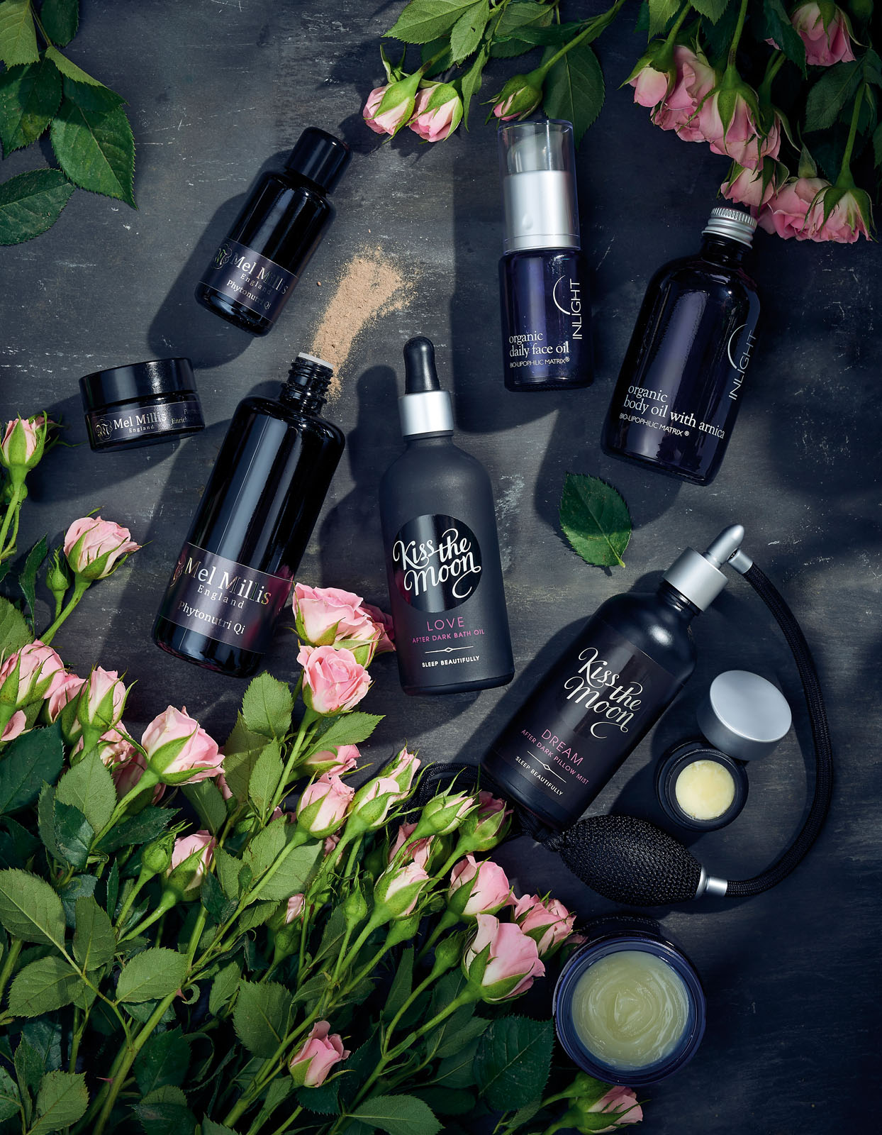 Black beauty products on a dark background with flowers