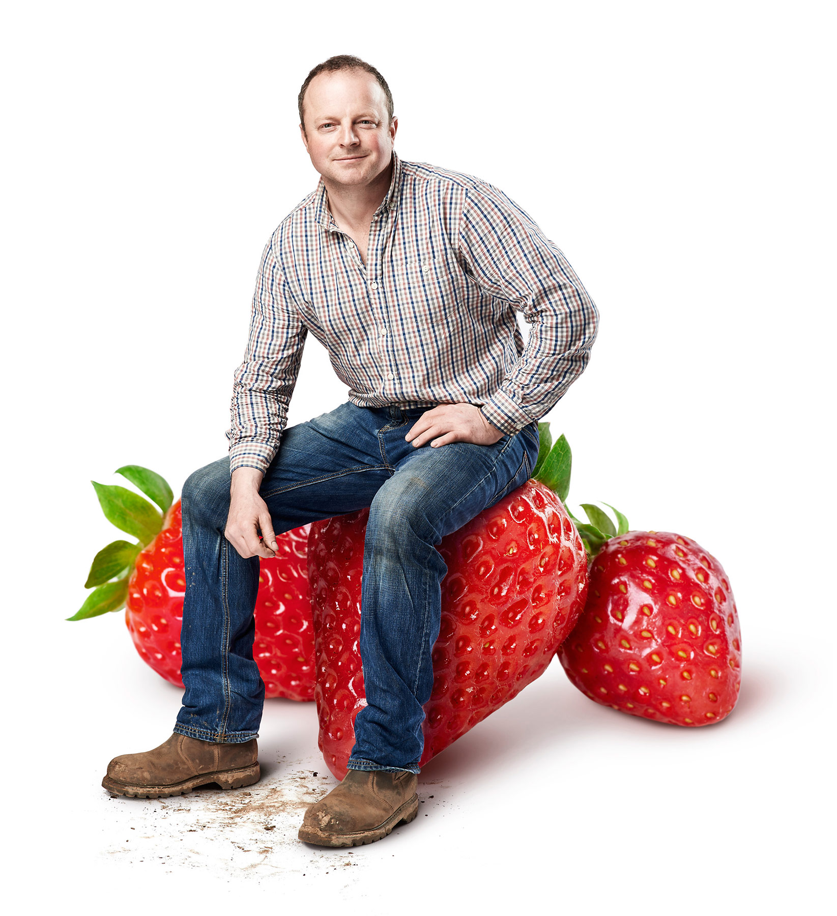 Farmer Charlie Tacon sitting on a giant strawberry