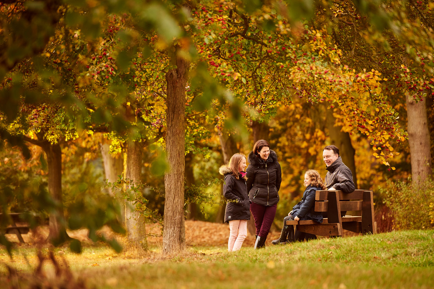 A family taking on a bench in the Autumn