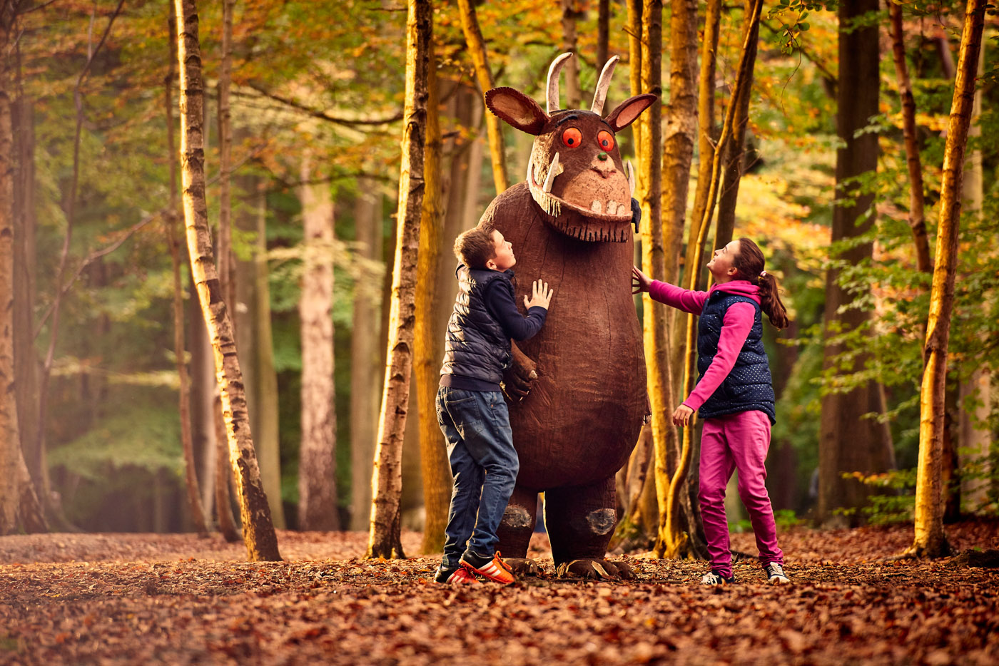 Two kids playing with a statue of the Gruffalo
