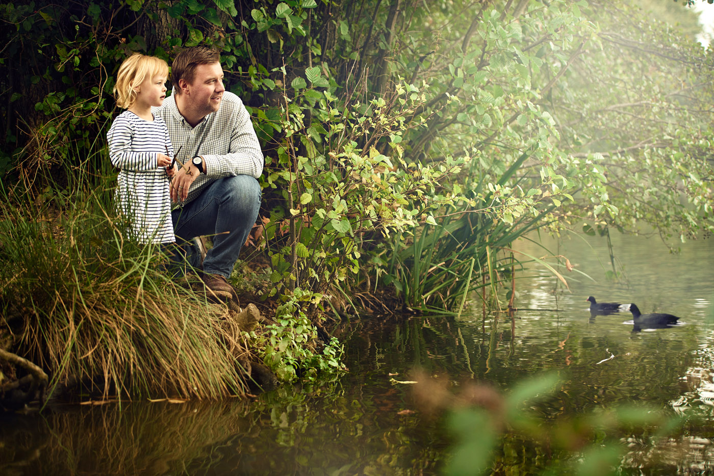Father and daughter looking out over a pond
