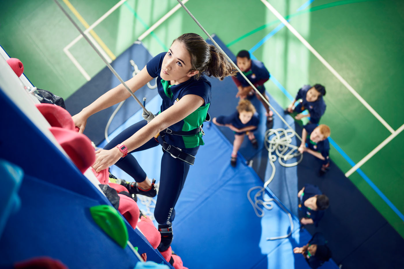 A student climbing high on the climbing wall