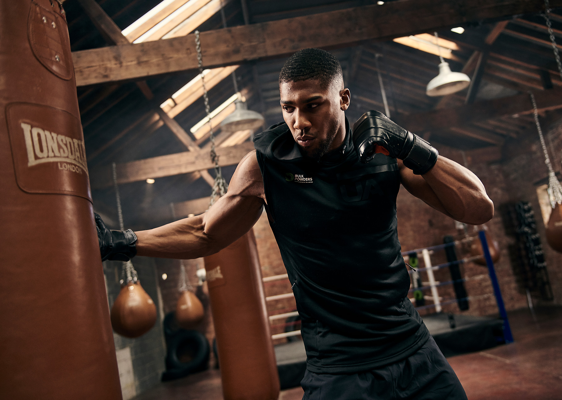 Anthony Joshua unleashing a punch on a bag