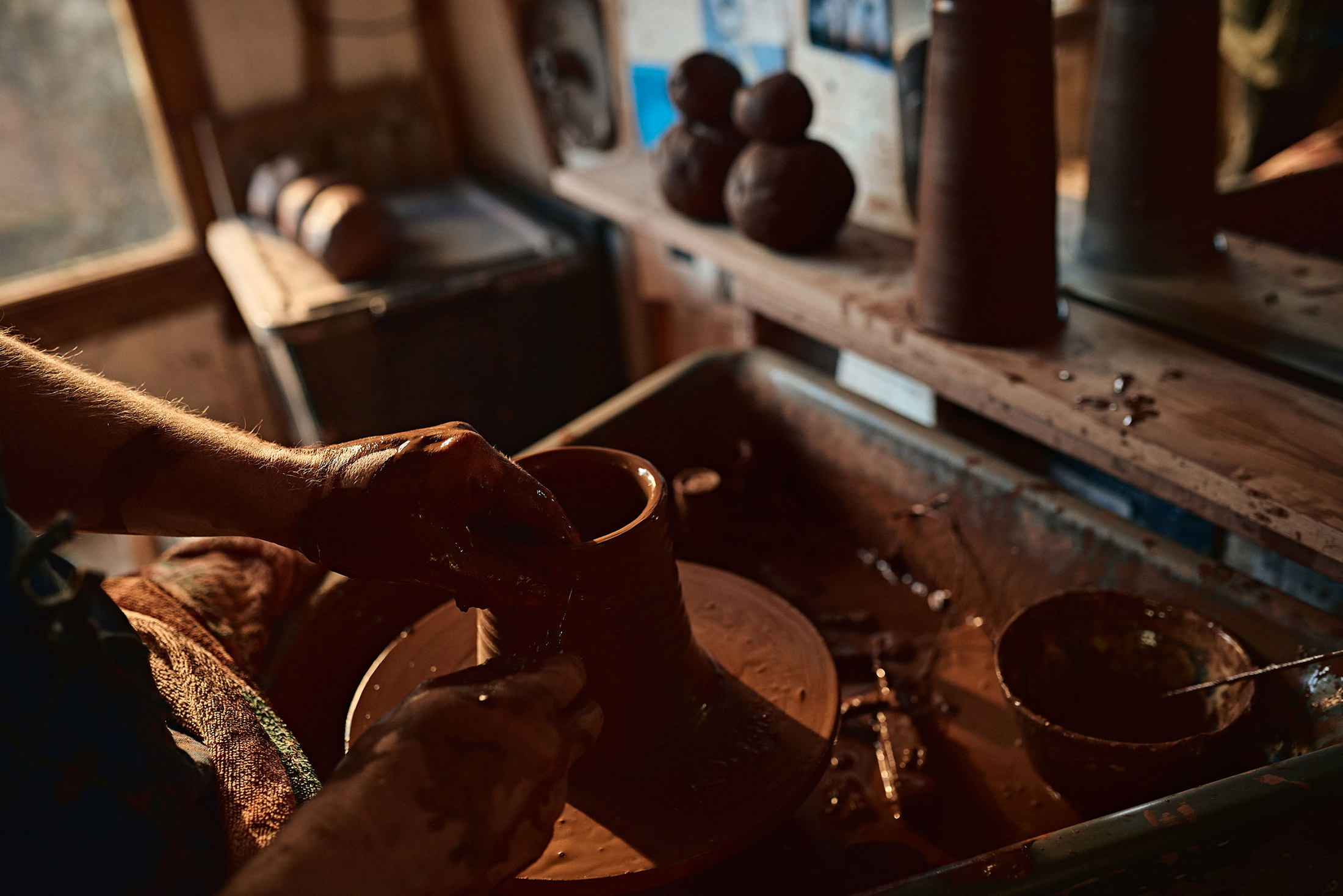 Close of of a craftsman creating a hand thrown jug from clay