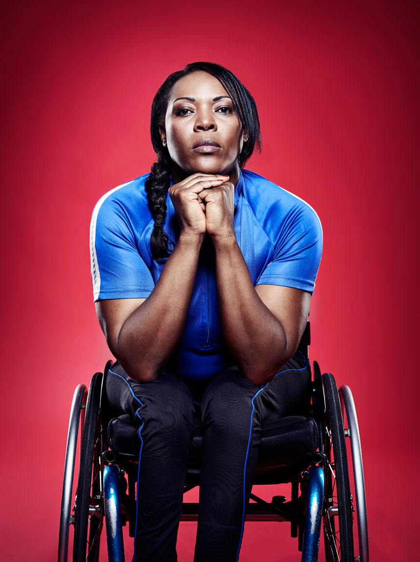 Anna Wafula Strike in her wheelchair on a red background