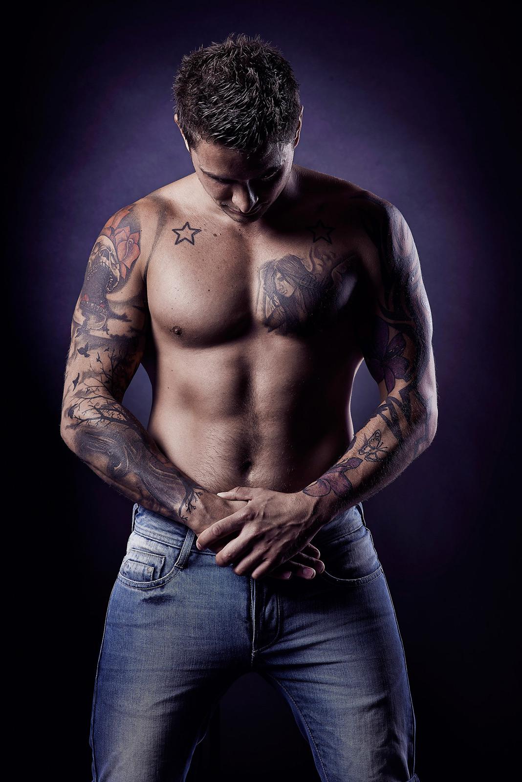 Man with shirt off showing tattoos and looking down