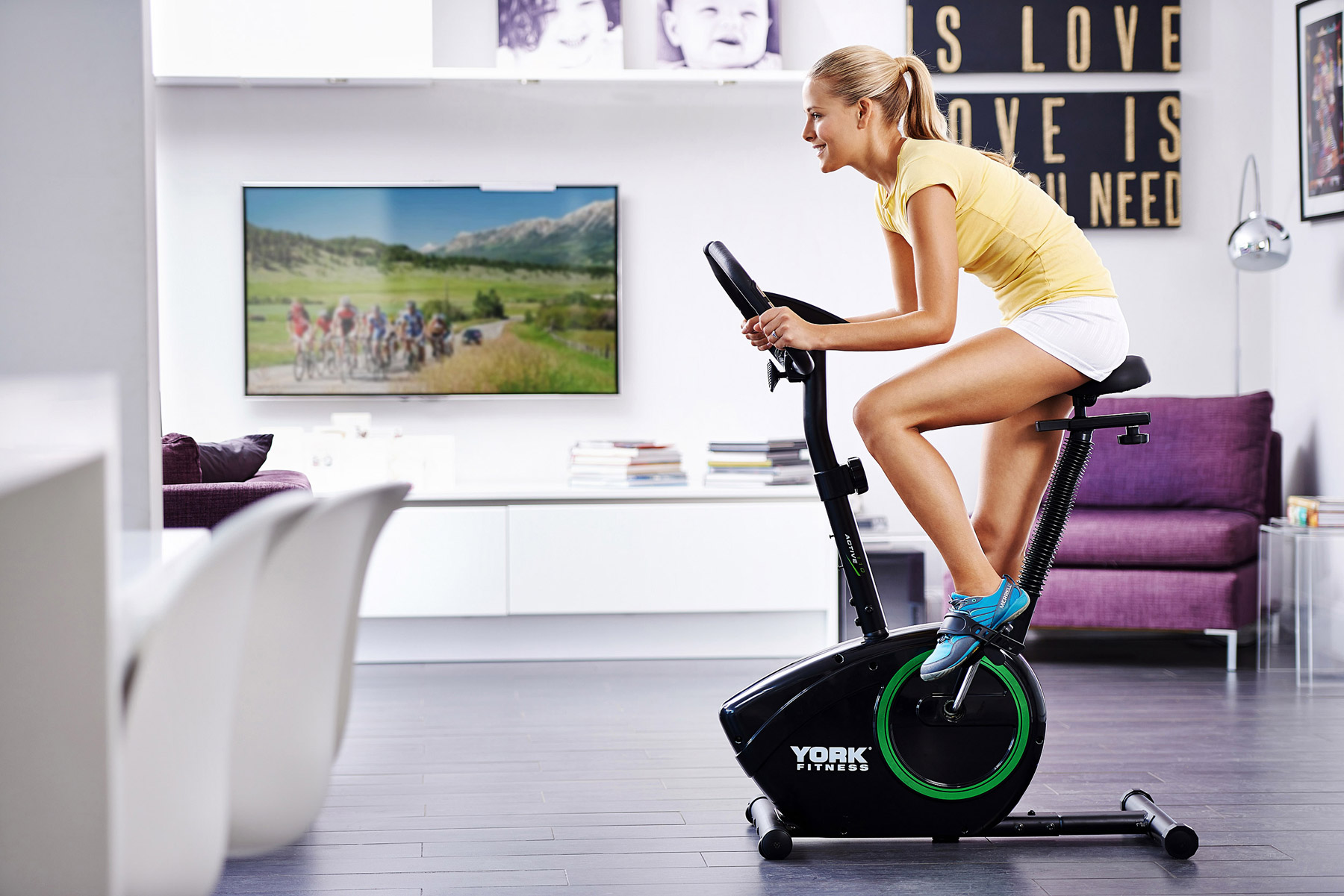 Lifestyle image showing a woman on an exercise bike in the home