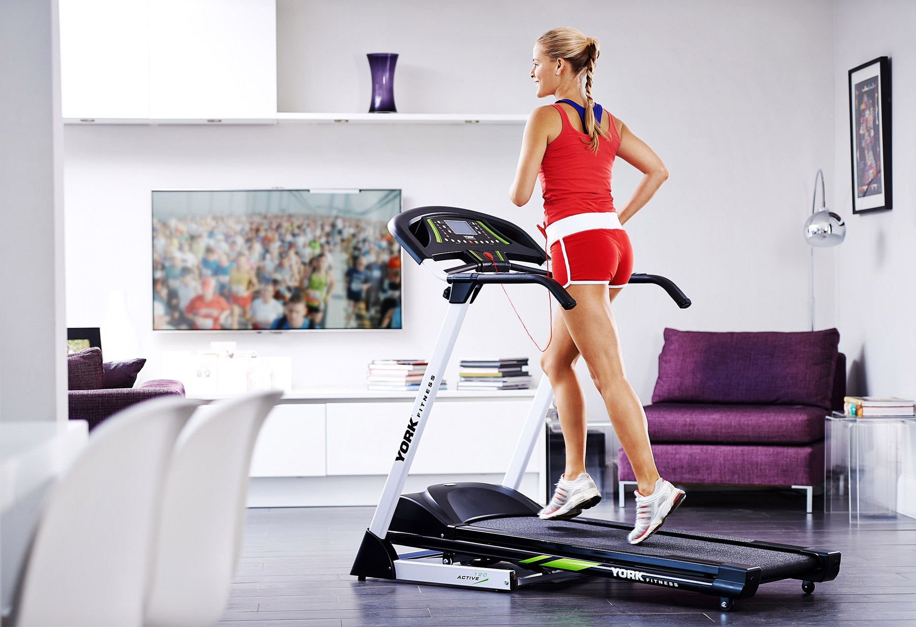 Lifestyle image showing a woman on a running machine in the home