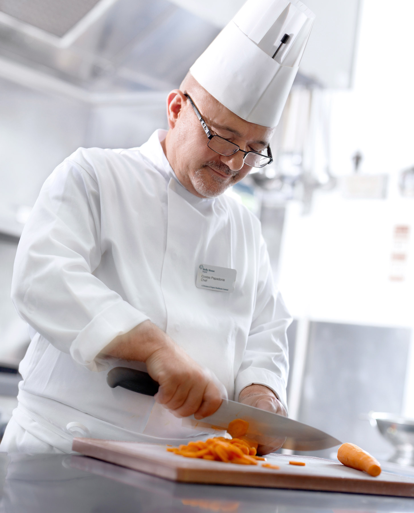 Chef chopping carrots in the hospital kitchen