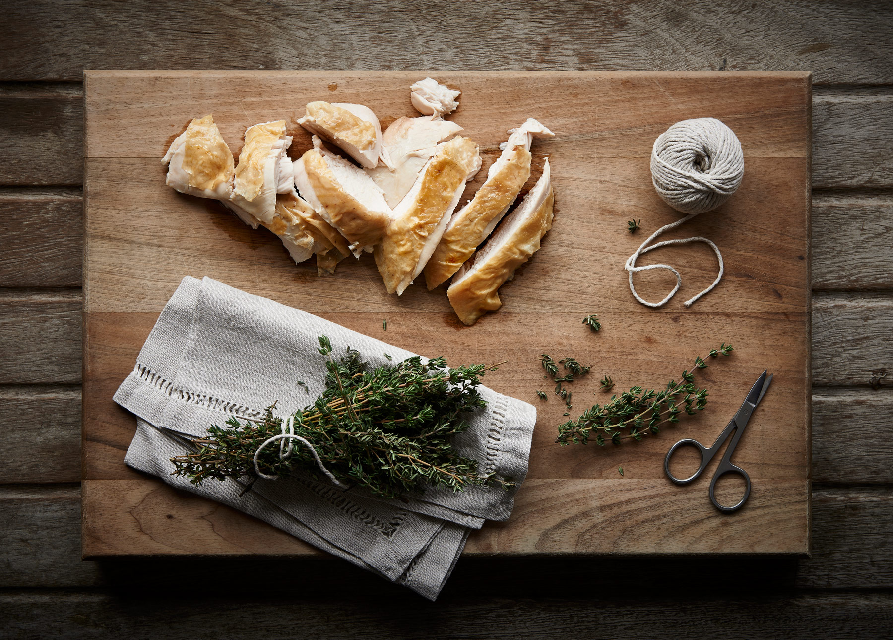 Chopping board with sliced chicken and thyme