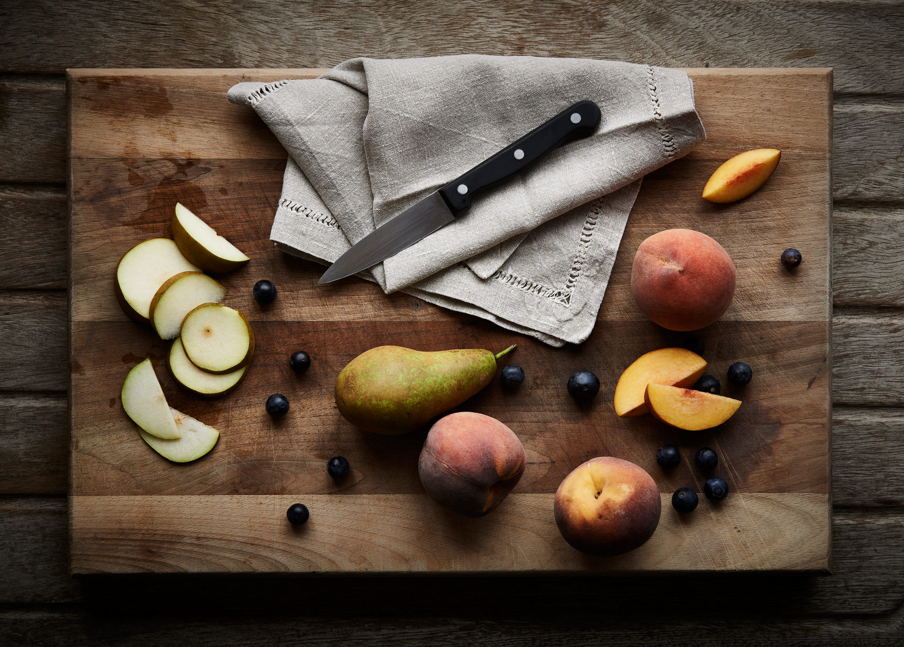 Chopping board with sliced pear and apricots