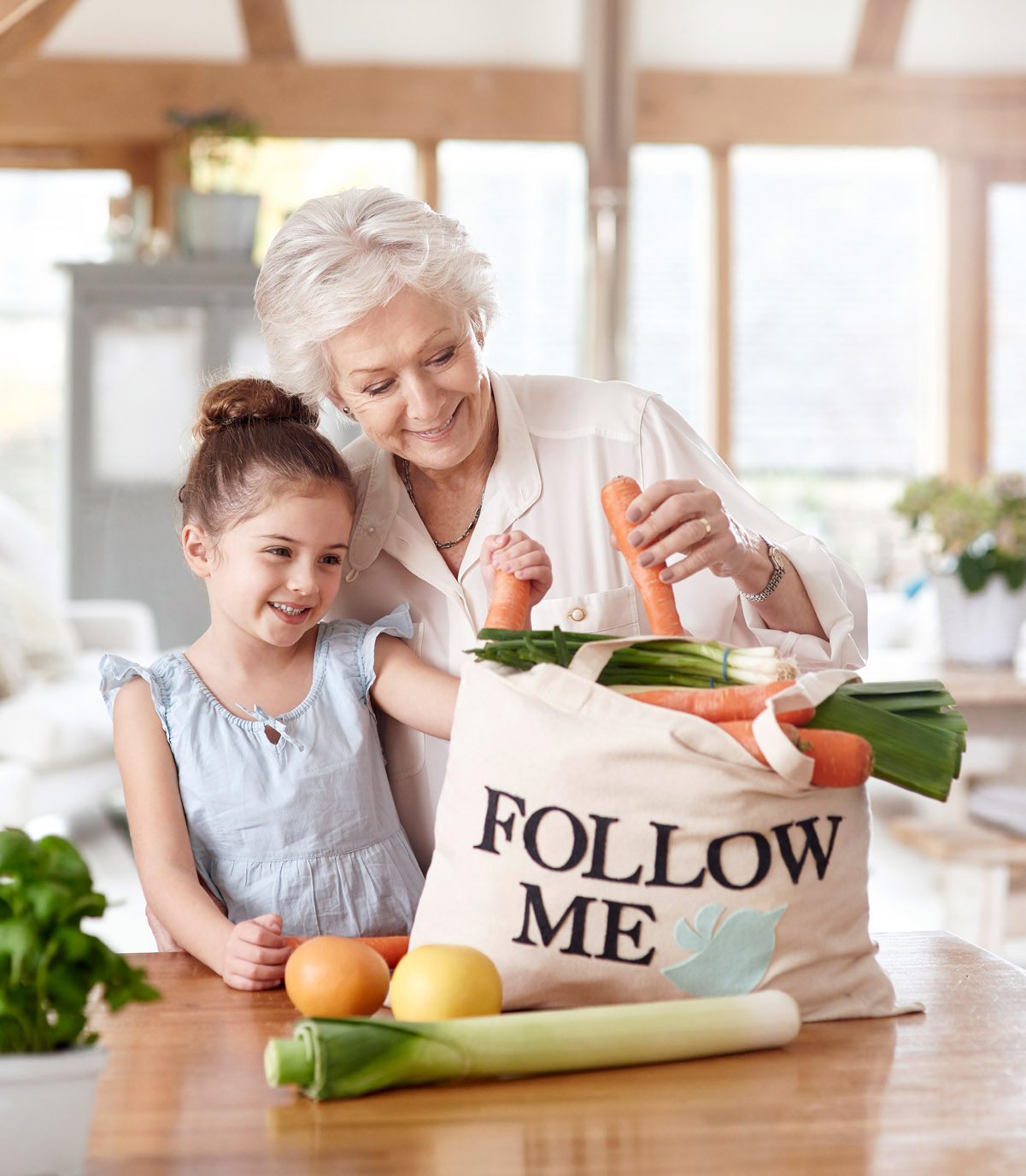 A grandma and her granddaughter unloading the shopping