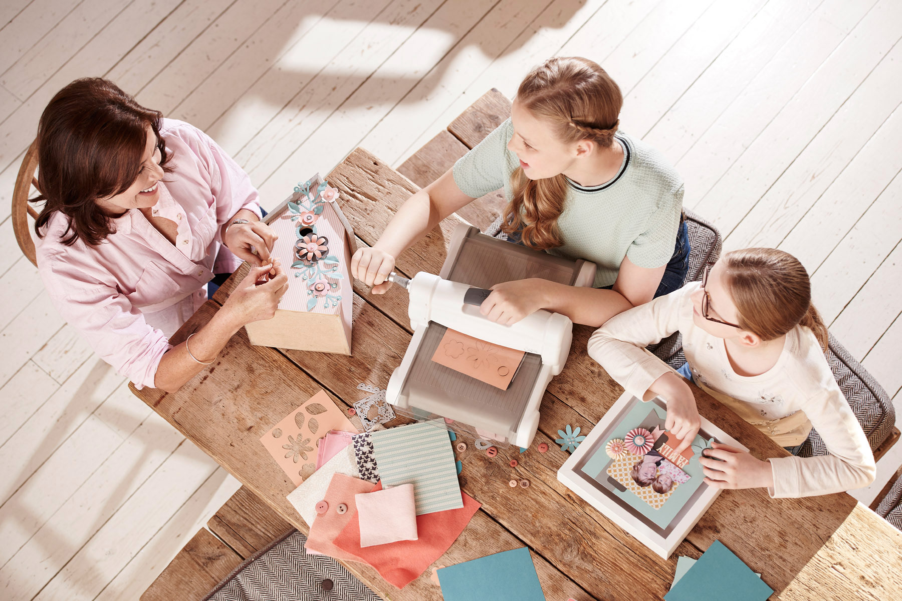 A mum and her two daughters crafting at a table, shot from above