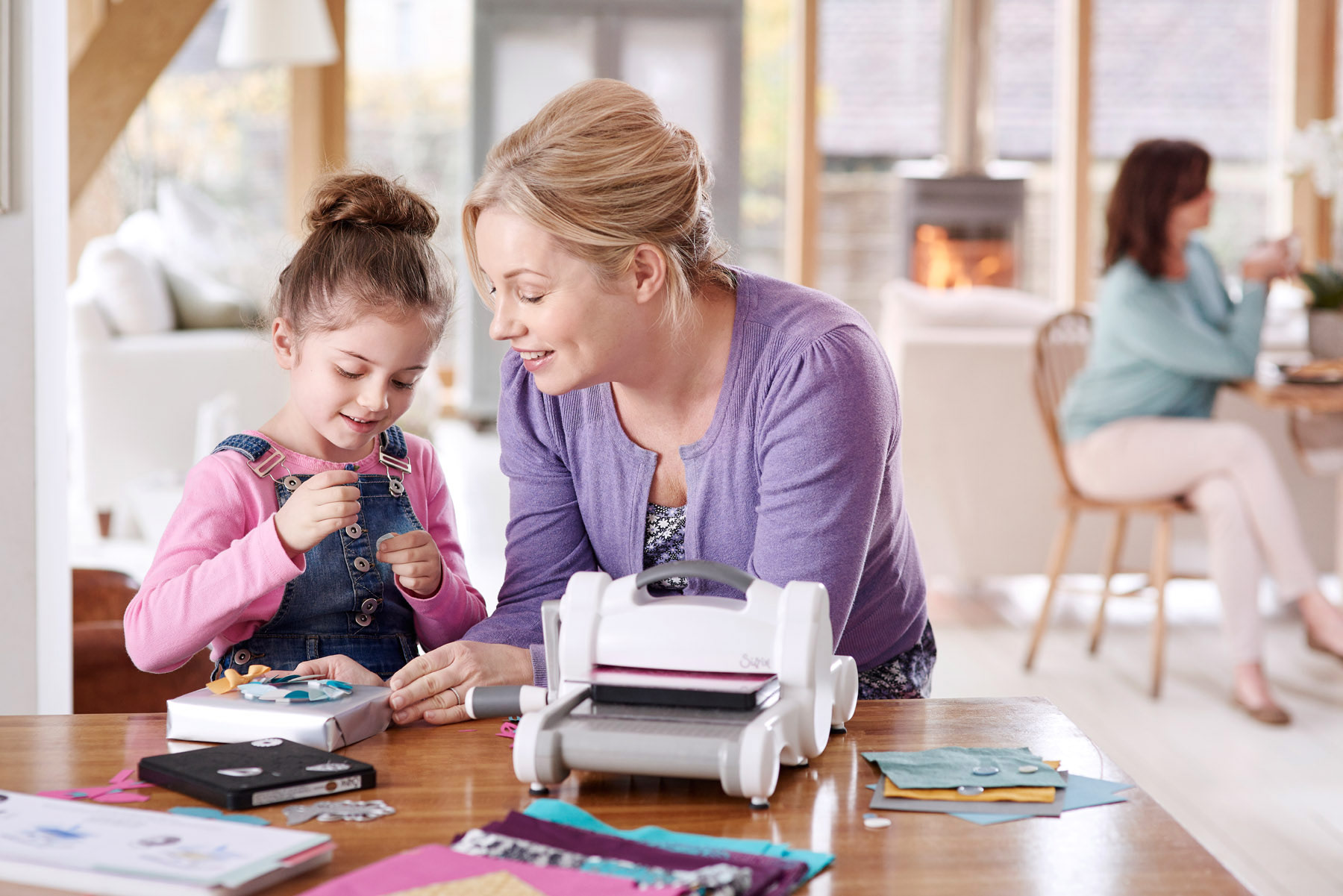 A mum and her daughter crafting at the kitchen table