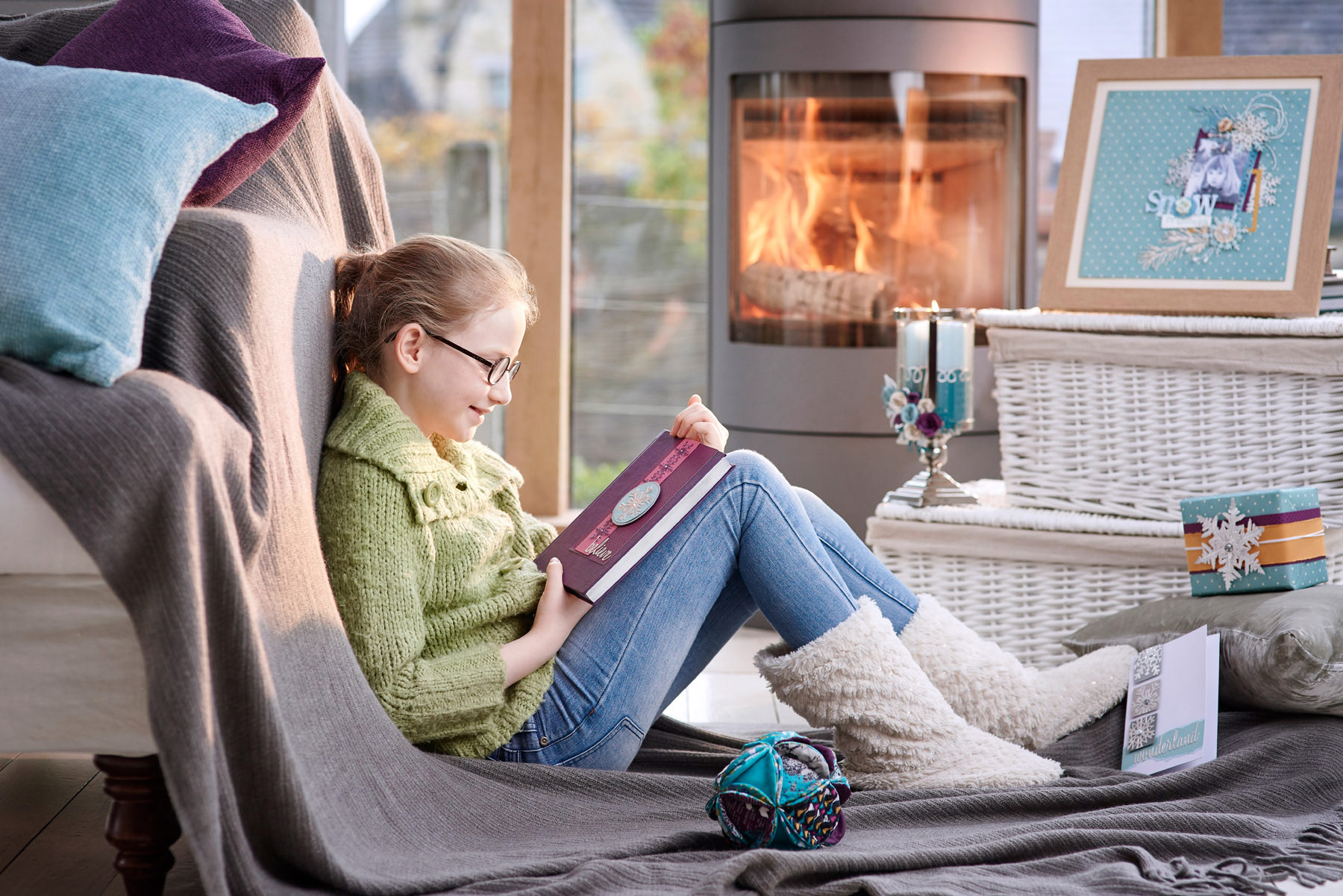 A young girl reading by the fire