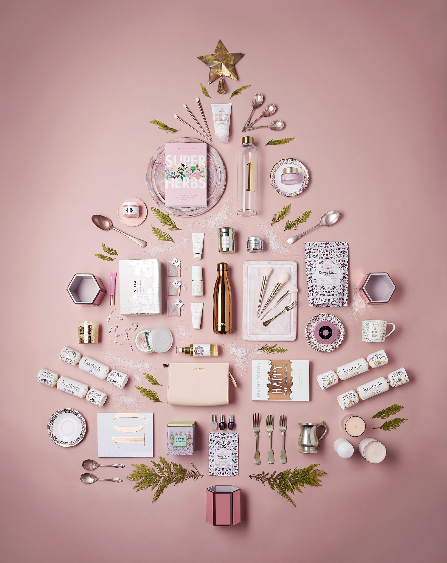 Christmas beauty products arranged in a Christmas Tree shape on a pink background