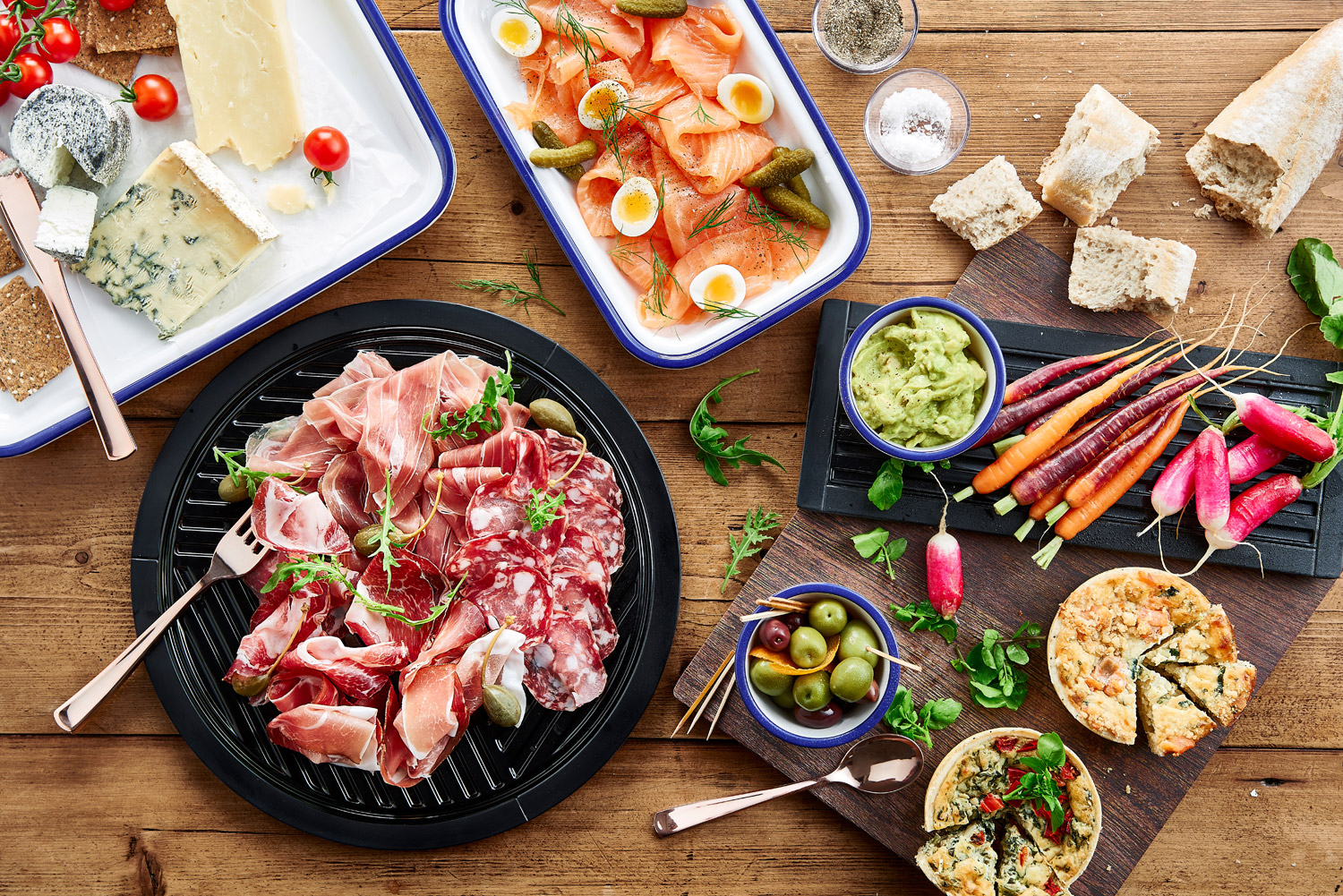 Overhead shot of various meats, cheeses, olives, quiches, bread and dip.