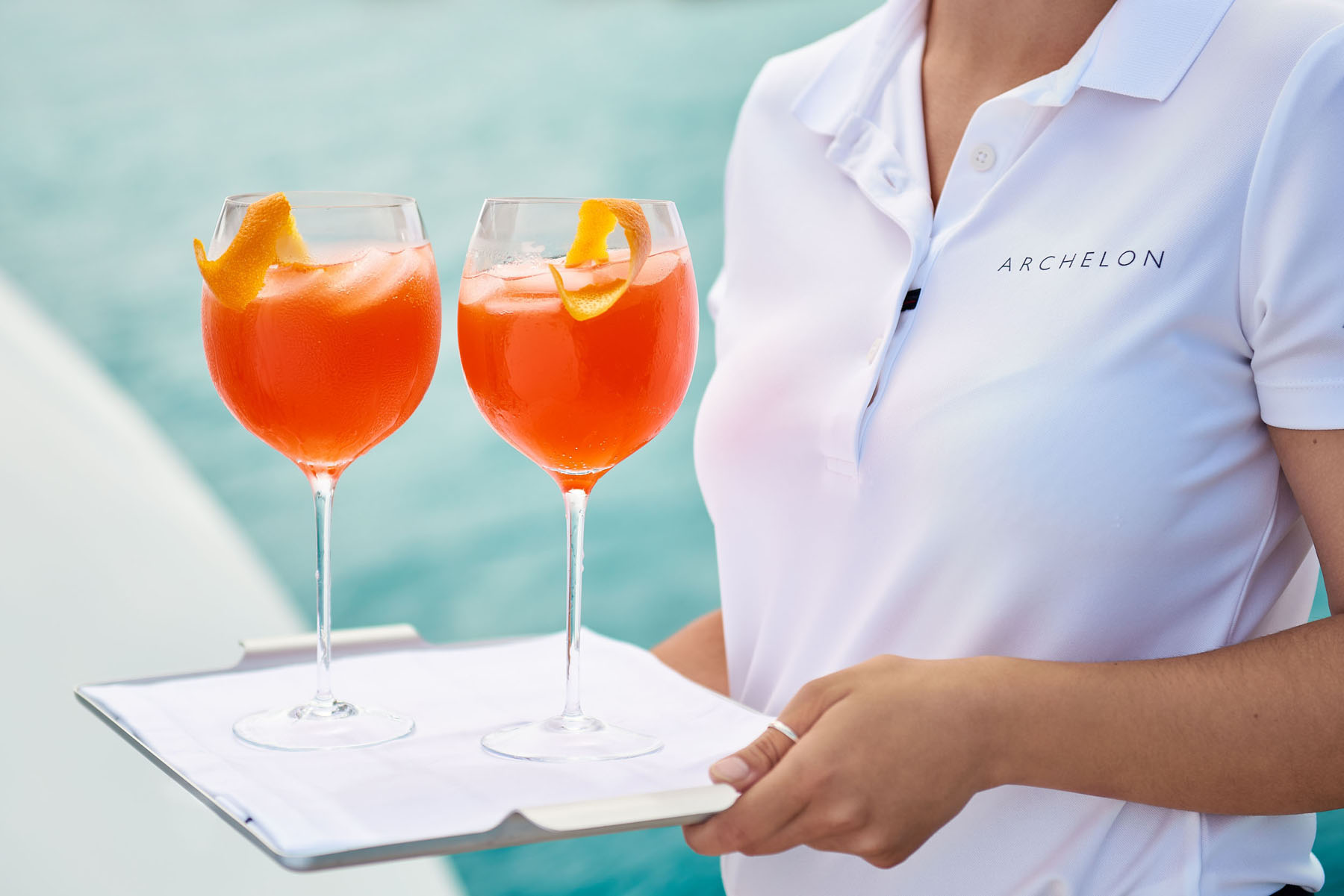 A woman holding a tray with two Aperol Spritzes