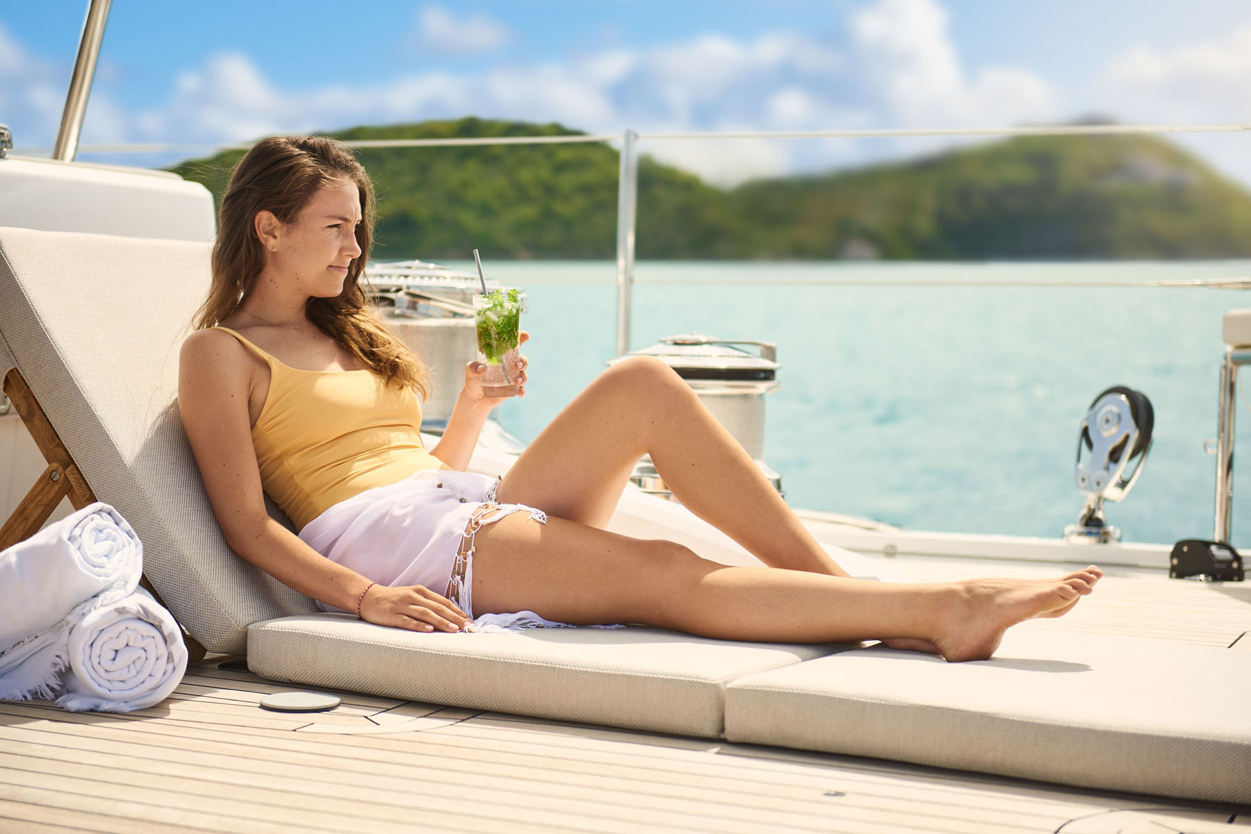 Woman relaxing on the deck of a super yacht drinking a cocktail