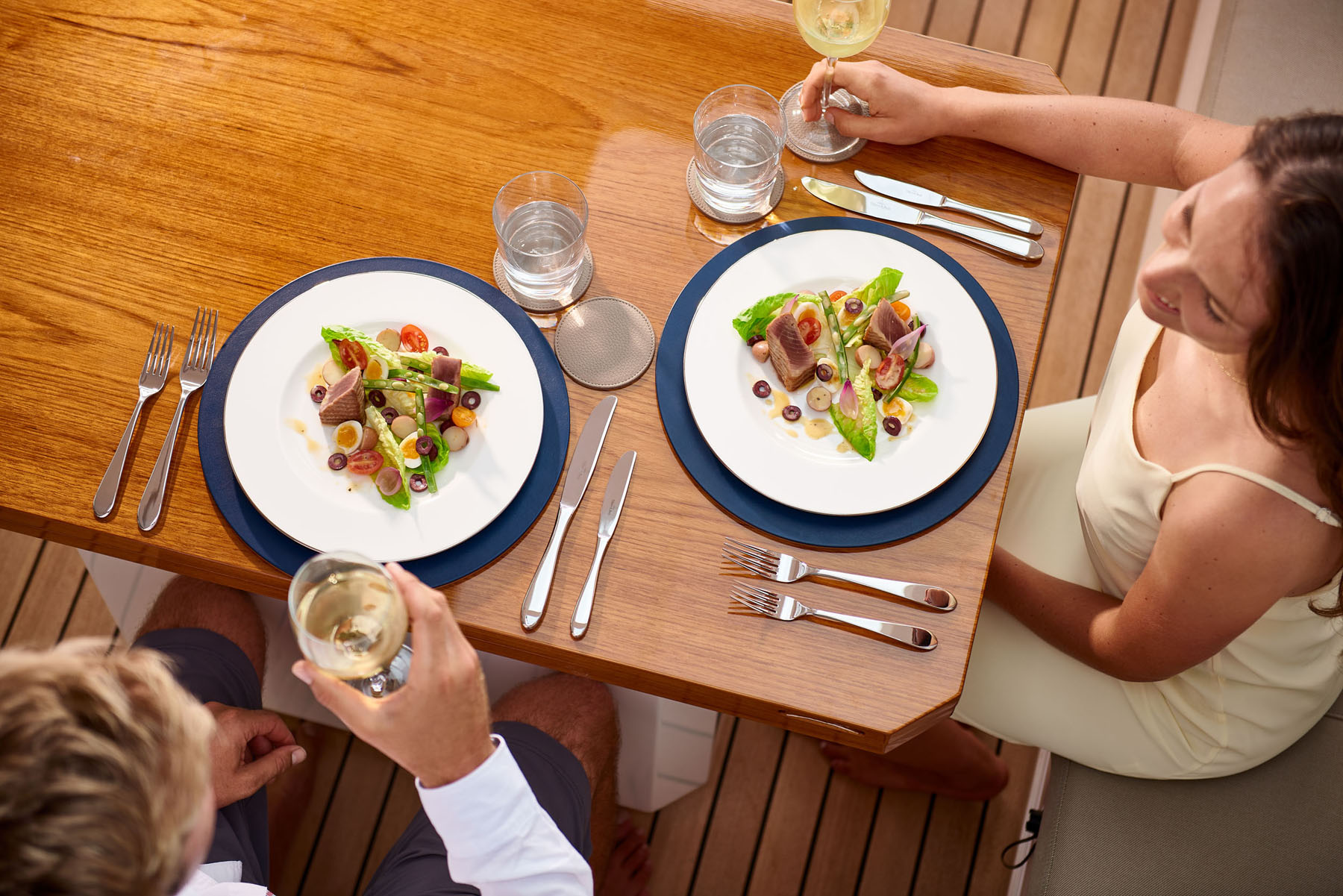 Overhead photo of a couple eating lunch on a yacht