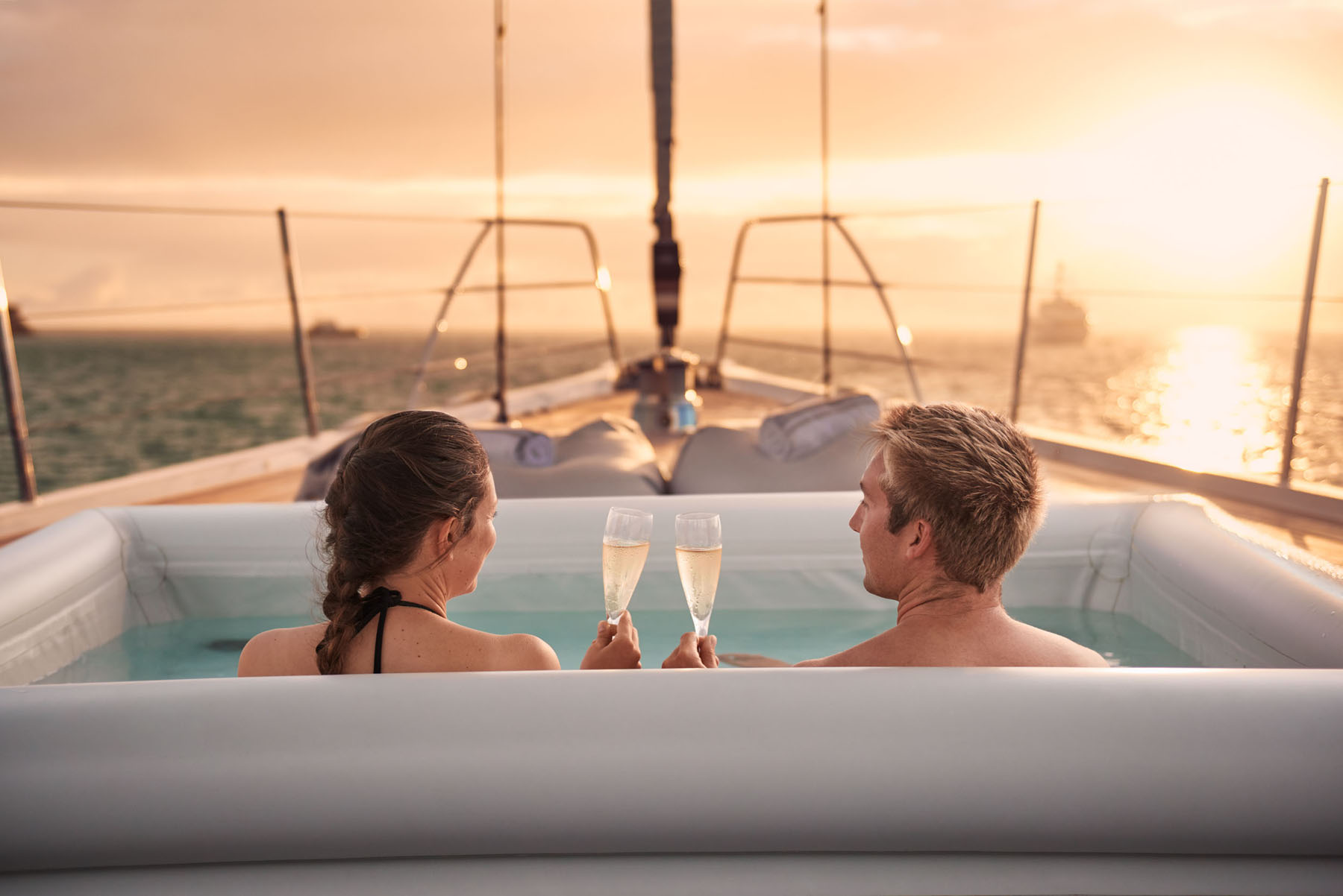 A couple enjoying champagne in the hot tub on a yacht as the sun sets