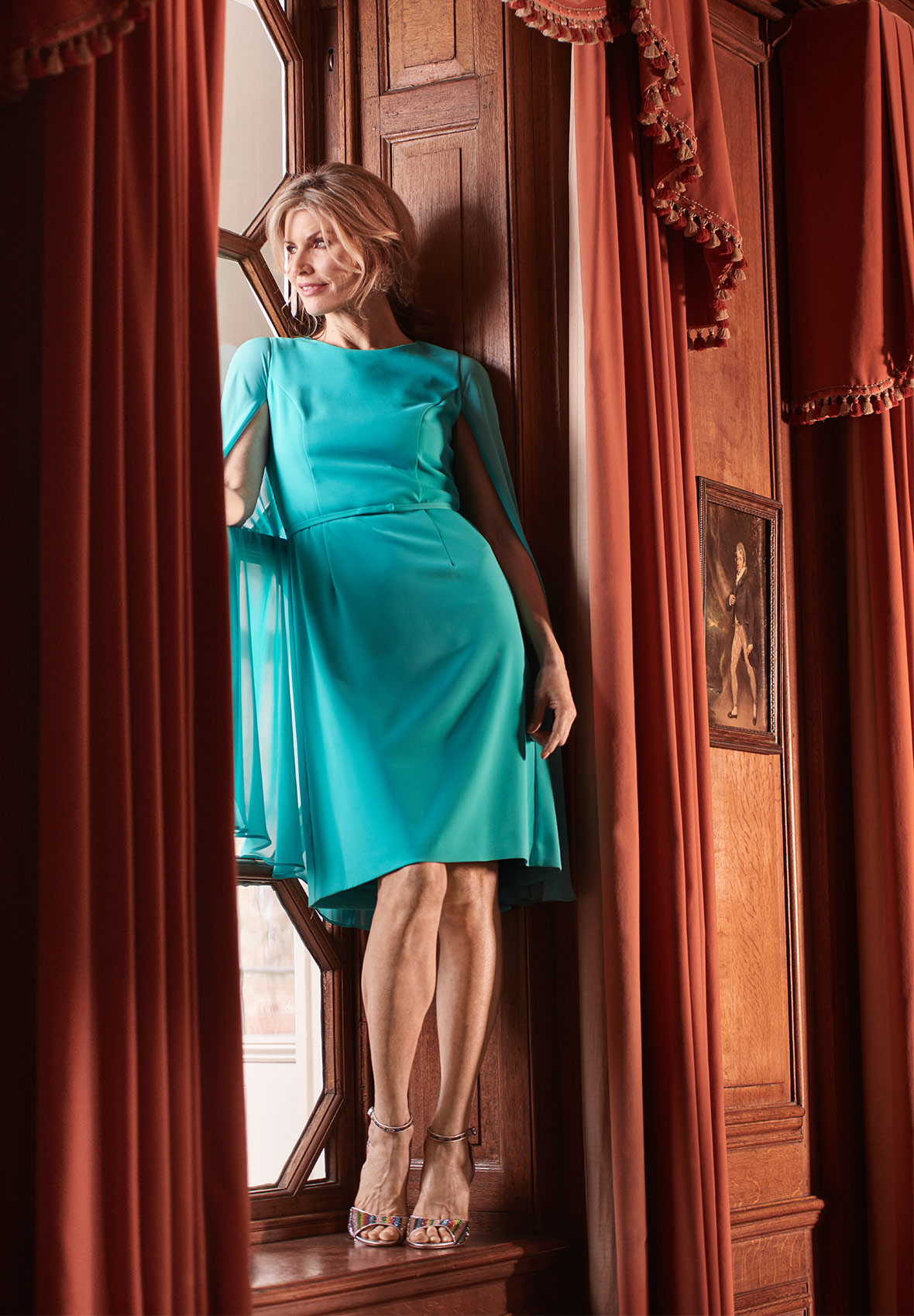 Model standing on a window sill wearing a teal dress